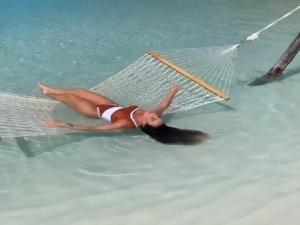 Nicole Bahls relaxa no mar das Maldivas.